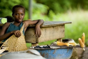 A teenager grills corn, Cote d?Ivoire.