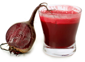 A glass of fresh beet vegetable juice isolated on white background.